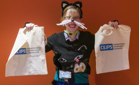 Conference delegate holds up two CILIPS Tote bags