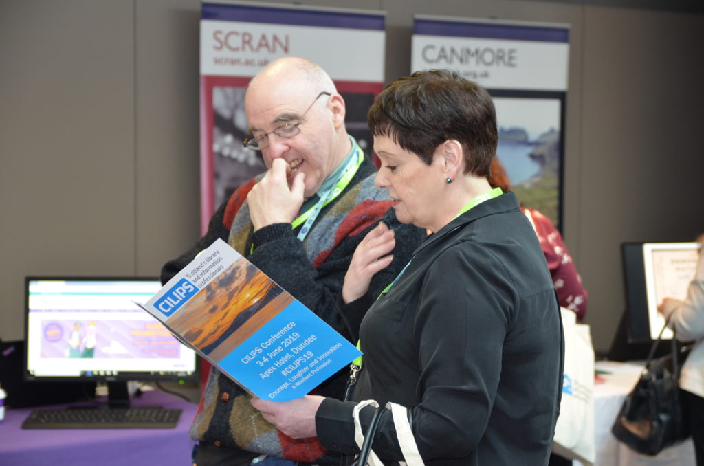 Conference attendees read programme