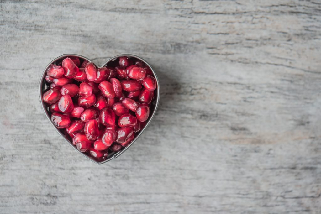 Heart bowl filled with pomegranate seeds