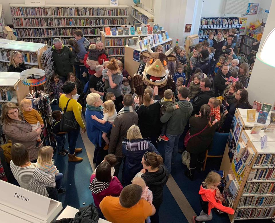 a crowd of adults and children with a lifesized Gruffalo character in the library