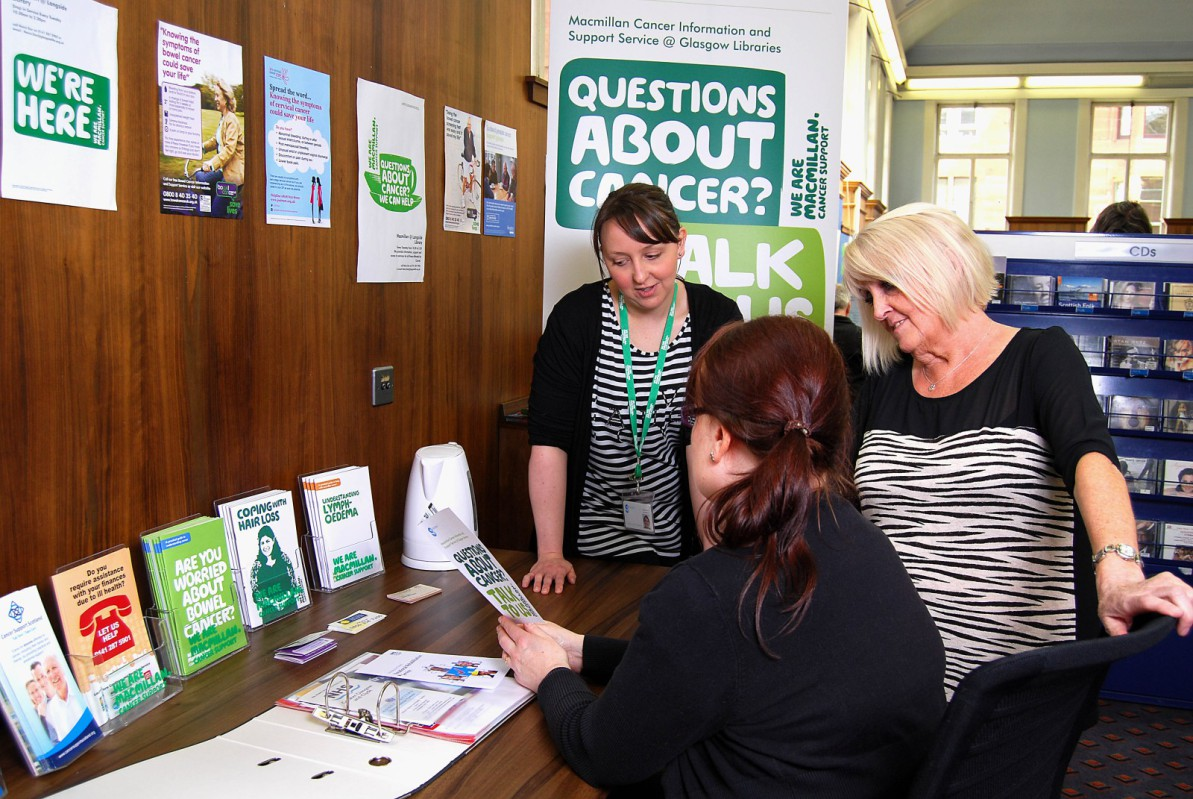 three women look at leaflets beneath a sign for Macmillan Cancer Support