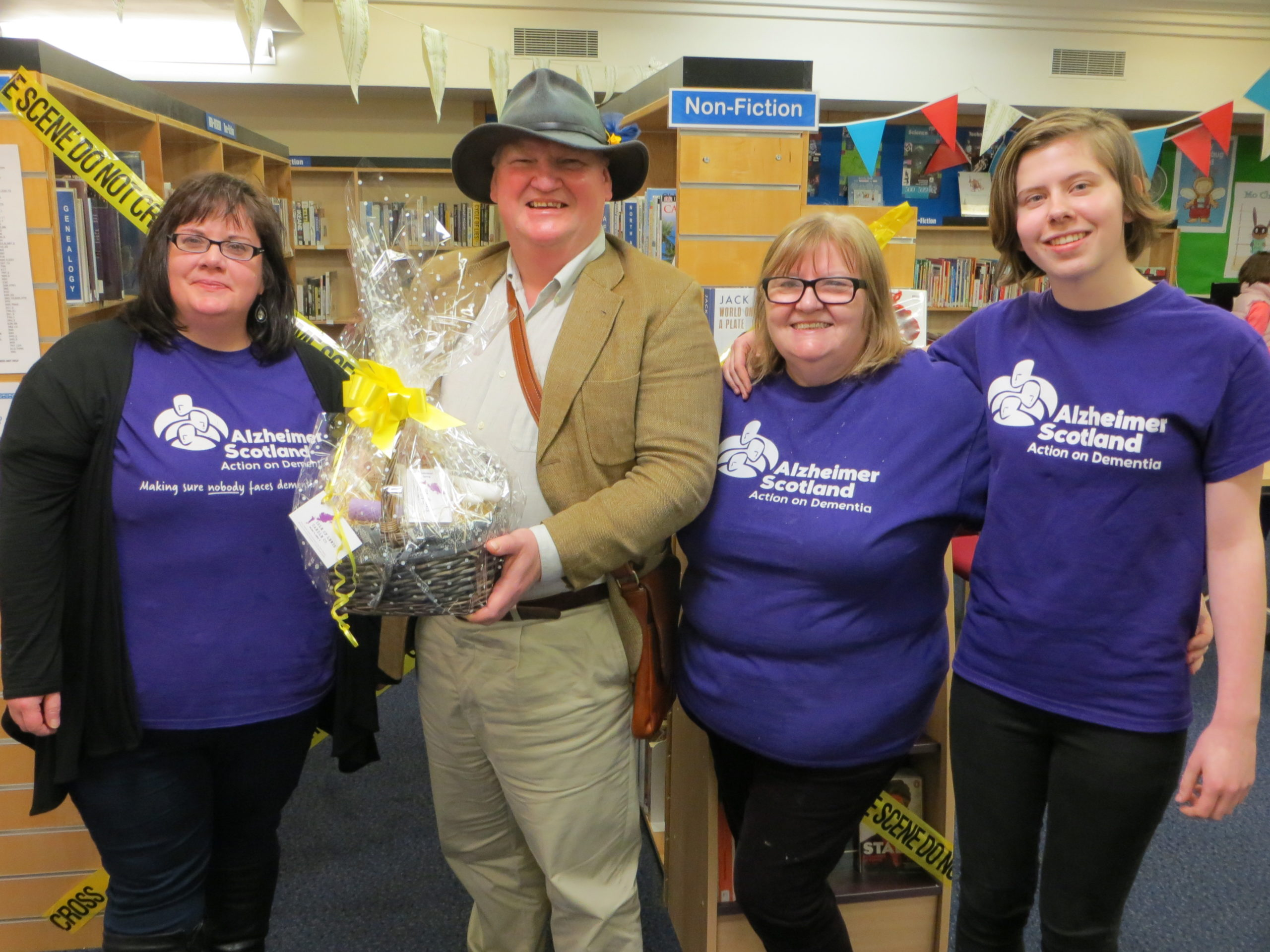 four people smiling in a library, holding up a prize and wearing Alzheimers Scotland tee-shirts.