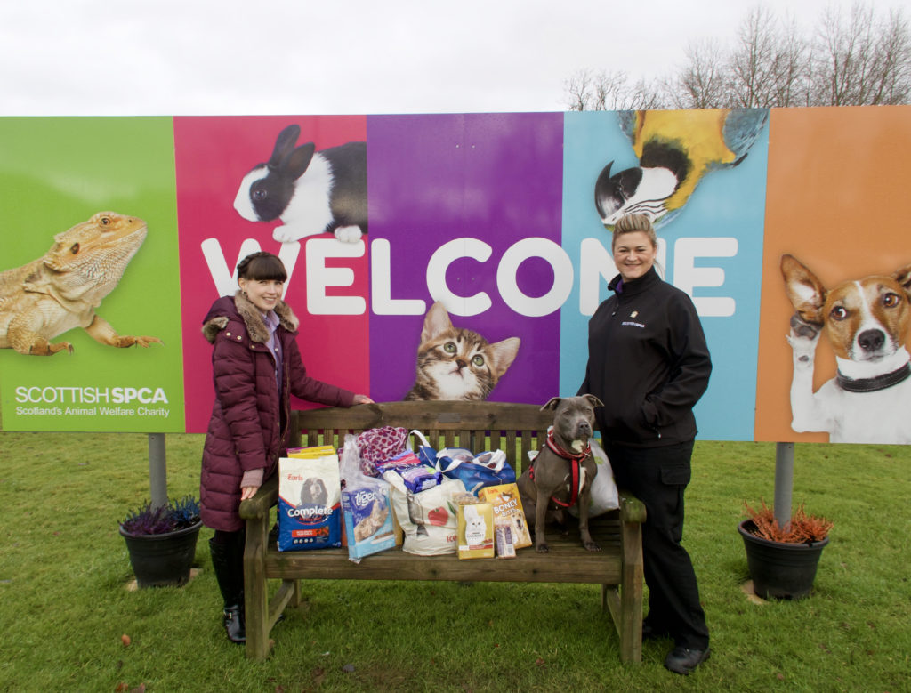 two women and a dog standing beside a bench loaded with animal food and toy donations
