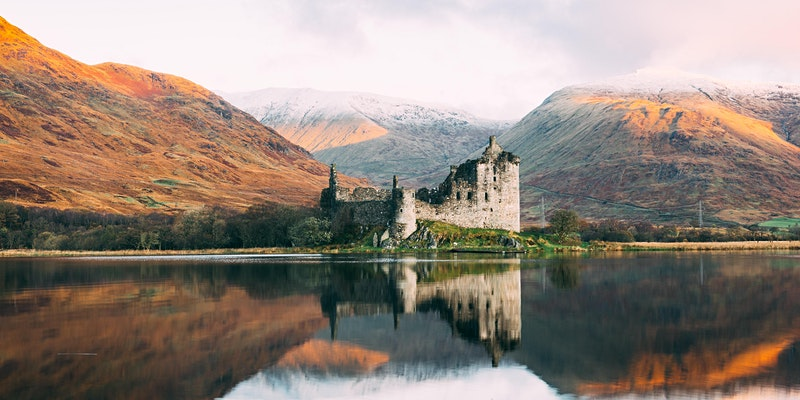 Eilean Donan Castle in Scotland - a medieval-style building with hills, mist and a loch surrounding it.