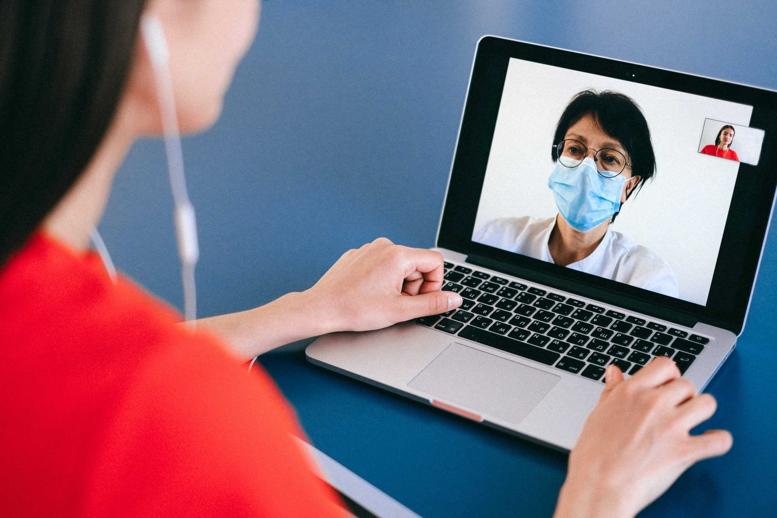 a woman with earphones in a video call with a doctor wearing a mask
