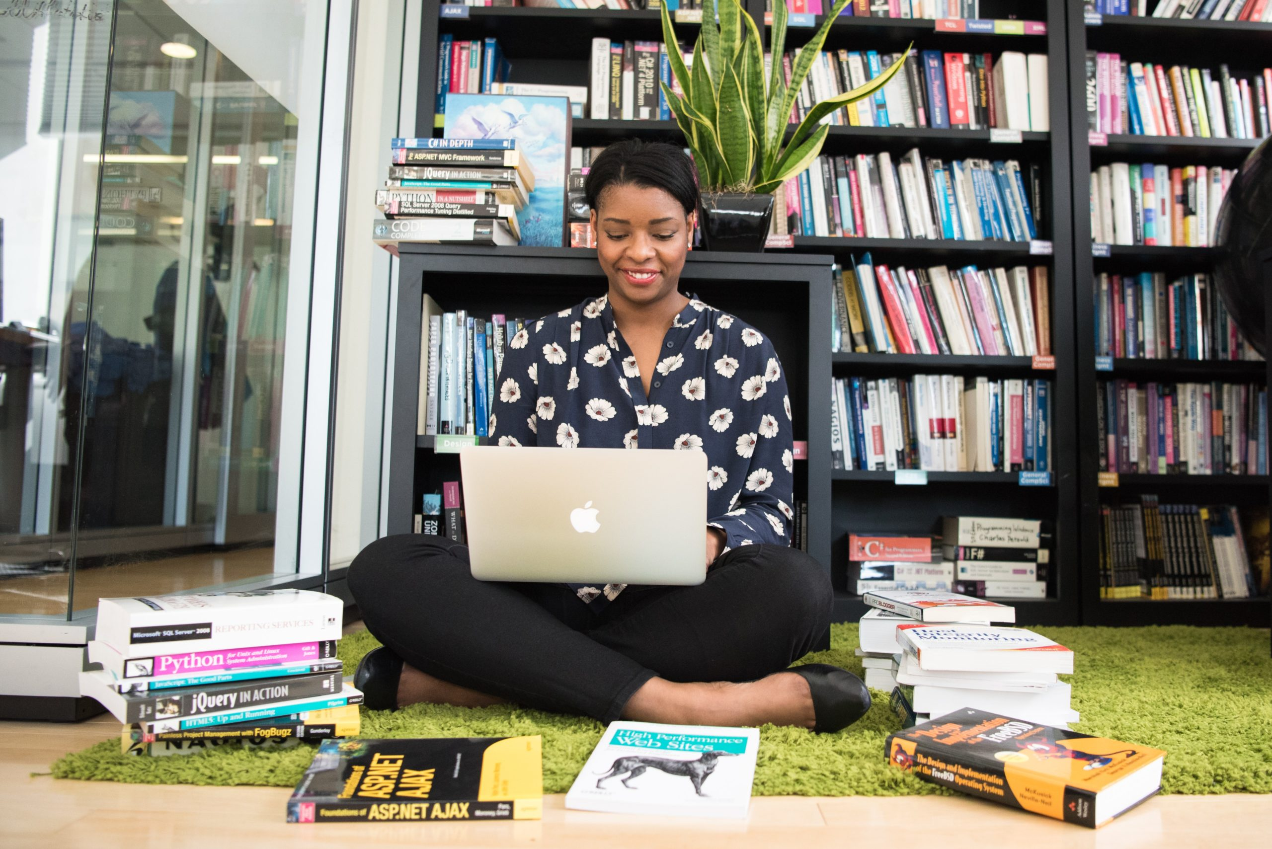 a woman sitting crossed legged on a library floor. surrounded by books and holding a laptop