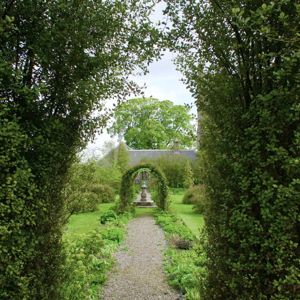a hedgerow archway looking down a path with a sculpture and tree beyond it