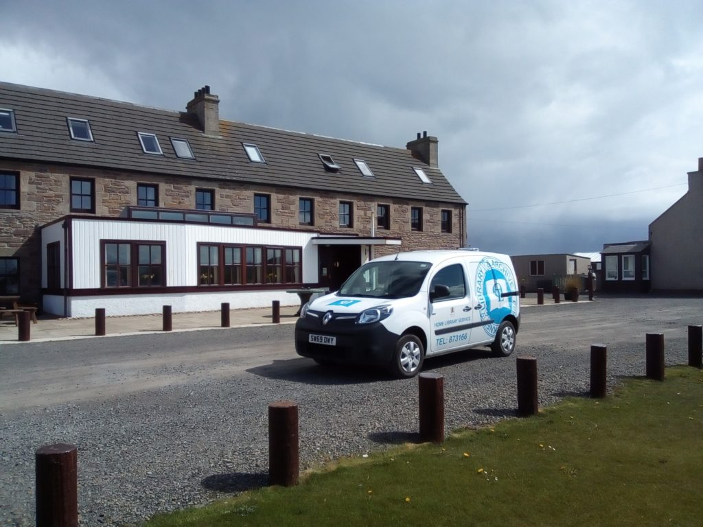 A white electric library van with a blue 'Orkney Library & Archive Service' logo