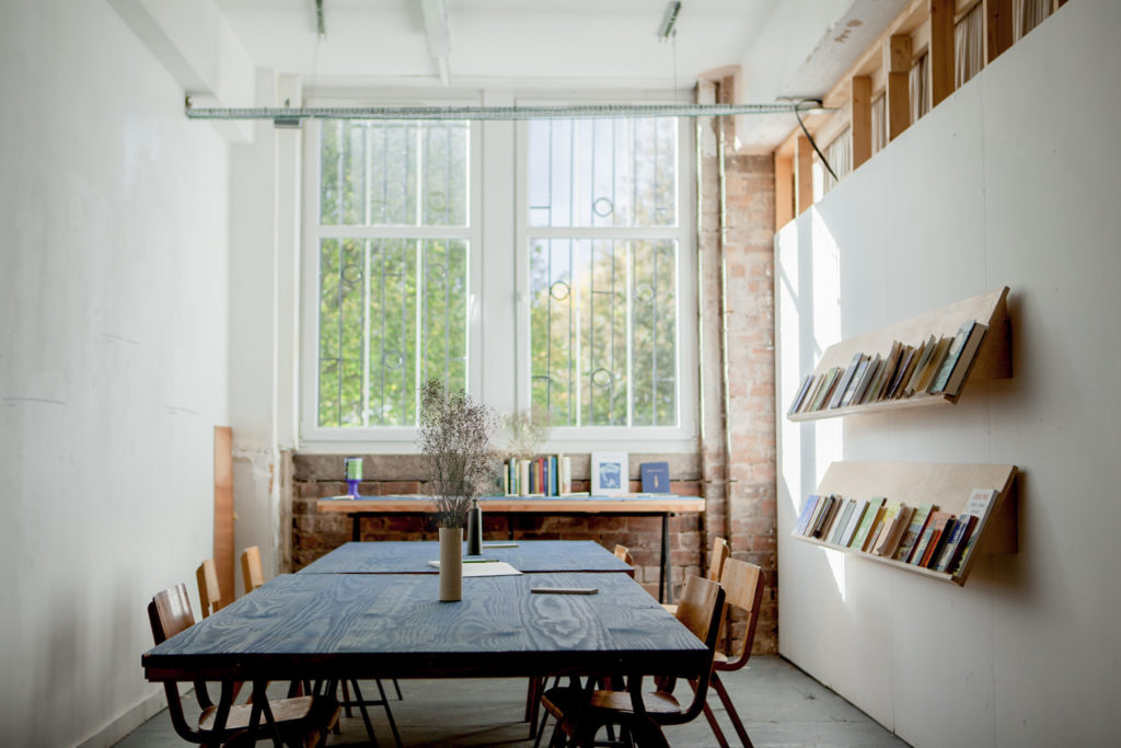 A room with white walls and a large window, with a slate table to create a reading space and shelves of books