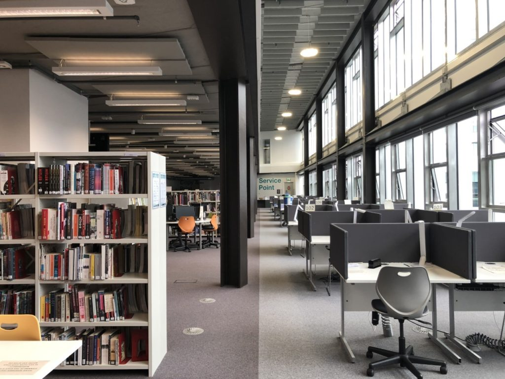 a large library space with shelves on the left and study spaces beside windows on the right